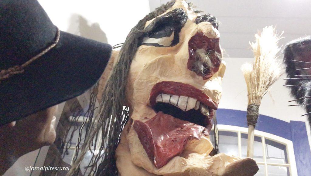 Bruxa Pereba com sua vassoura, língua retorcida e cabelo no nariz