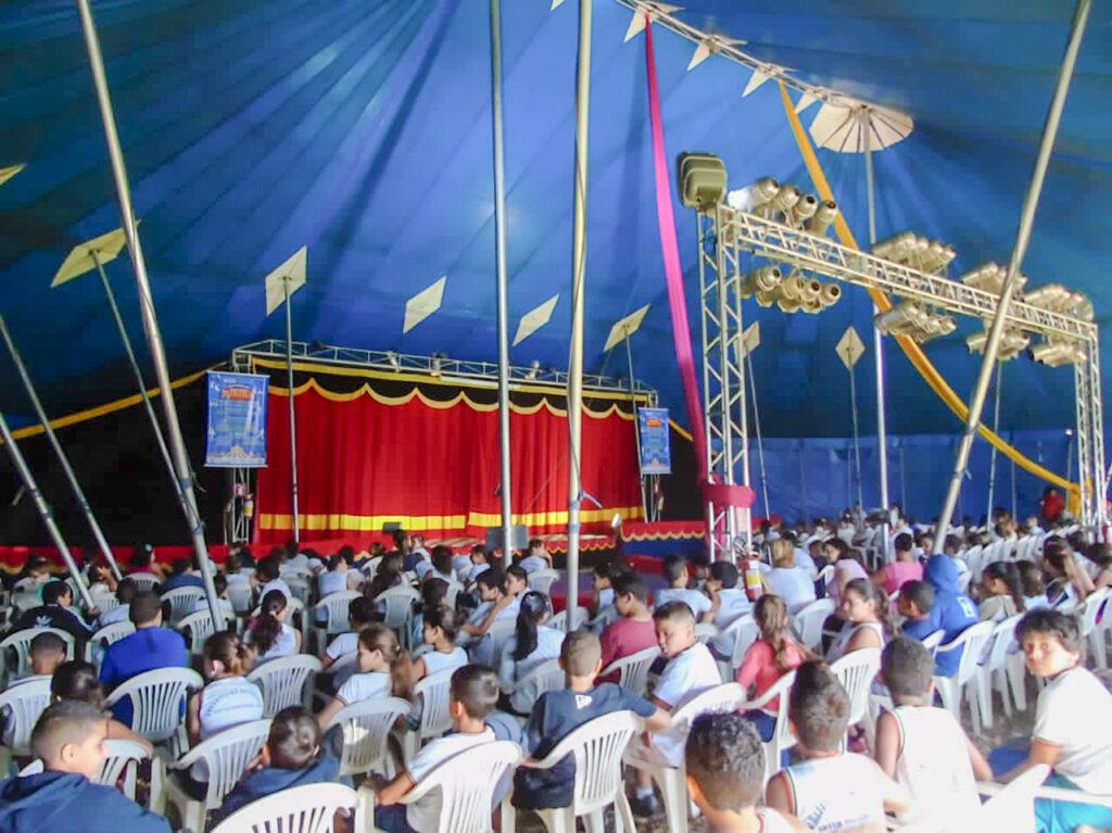 Dentro do circo centenas de crianças sentadas aguardam o espetáculo começar