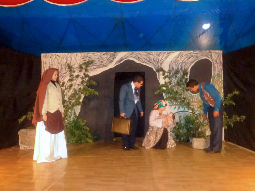 Cena com quatro atores representando uma freira religiosa, um empresário segurando uma pasta preta, olhando para uma mulher sentada com uma criança no colo e o pai da criança em pé olhando para a mulher sentada