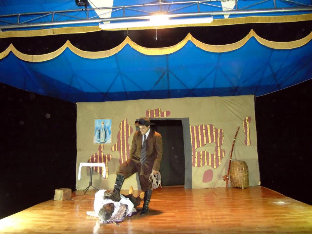 Um homem de chapéu de vaqueiro, terno, gravata, calça marrom e botas pretas está segurando uma corda na mão esquerda  enquanto pisa com o pé direito em um homem caído ao chão. O homem caído está com as mão na bota que está pressionando seu peito.