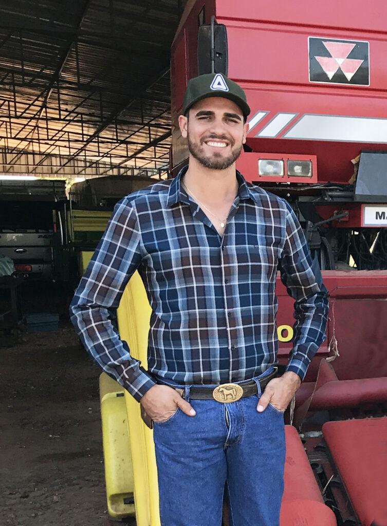 Edson no galpão onde guarda as máquinas, com as mãos no bolso, vestindo camisa de manga longa xadrez, calça jeans, cinto com fivela grande dourada e boné, sorri para a foto