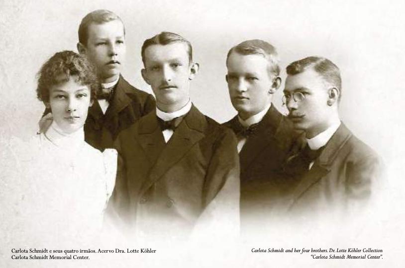 Carlota é a primeira à esquerda na foto, usando vestido branco e cabelo preso está a frente de seus quatro irmãos adultos, todos usando paletó preto