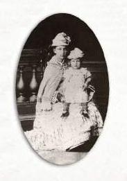 Catharina sentada em uma cadeira, usando vestido longo branco e chapéu branco, com a filha pequena em seu colo, usando vestidinho branco e chapeuzinho branco