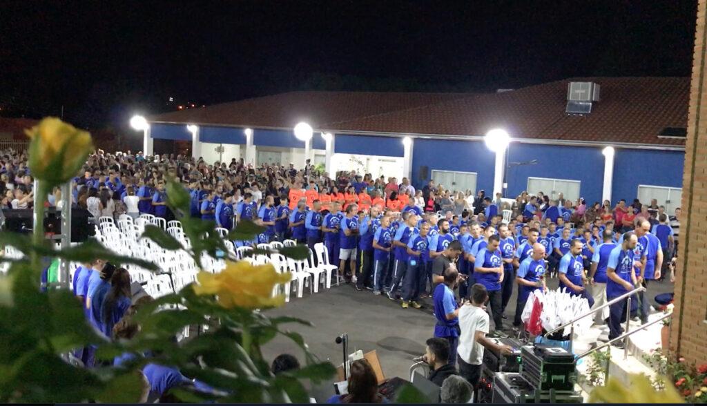 Em fila os romeiro seguem para o altar com uma rosa nas mãos
