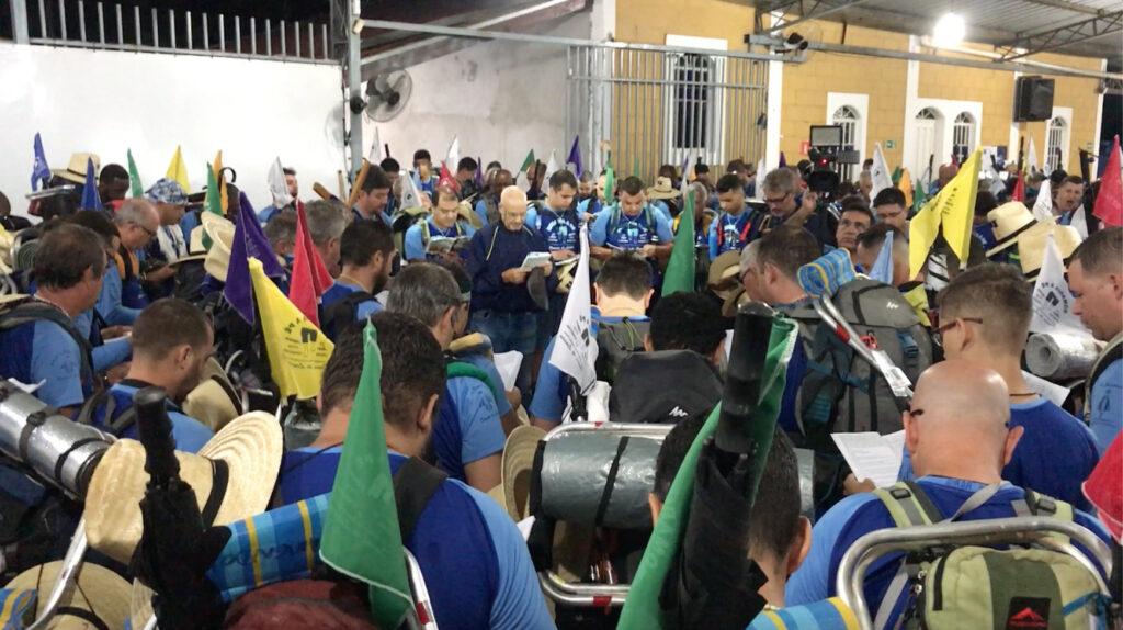 Romeiros, em pé, formando um círculo e no centro está Valdevino Vieira rezando o terço